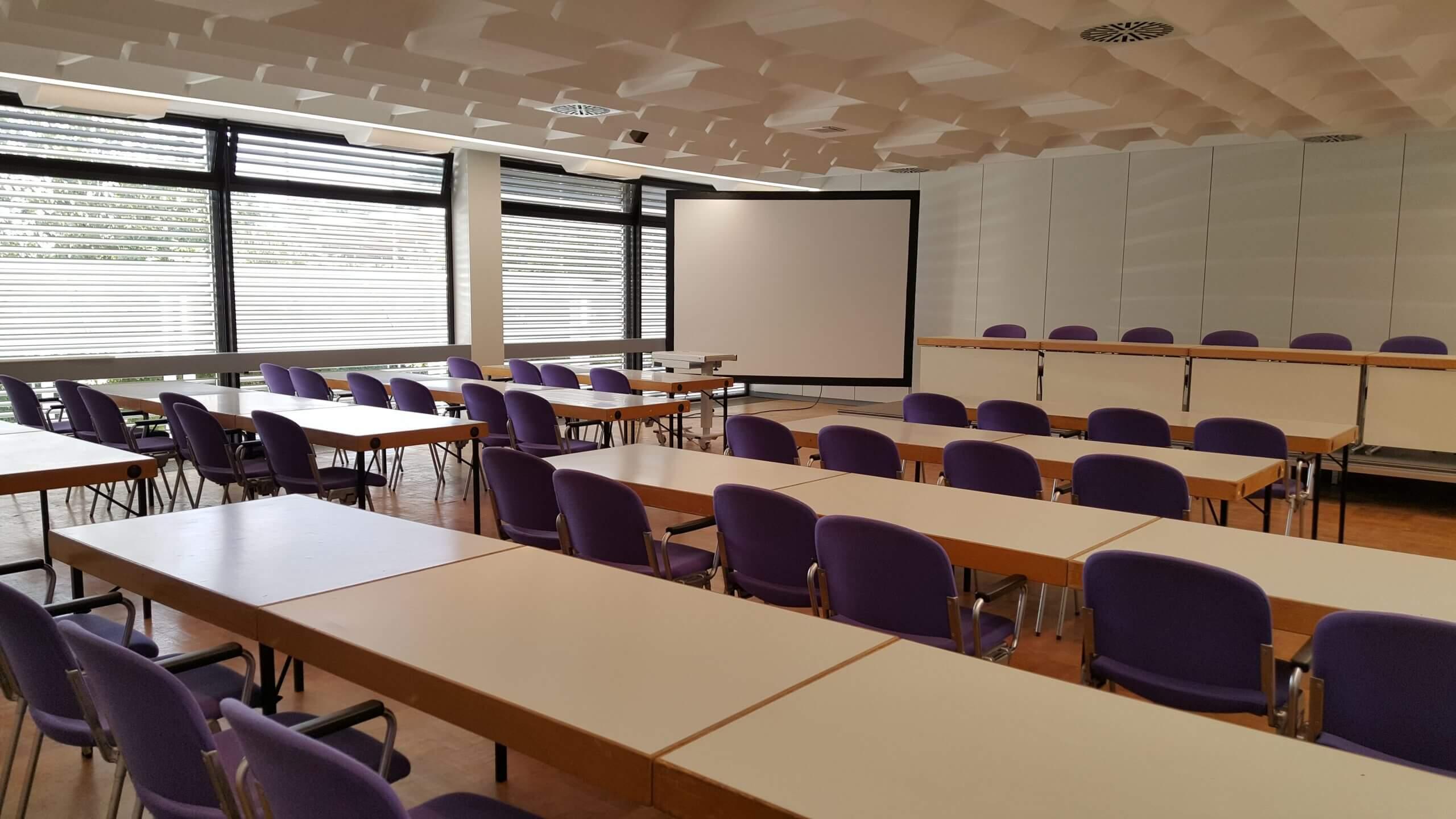 Saal 1 in der Saarlandhalle in Reihenbestuhlung mit Vorstandstisch und Leinwand