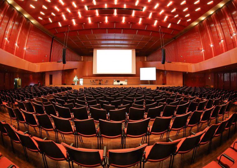 Grosser Saal der Congresshalle in Reihenbestuhlung mit Rednerpult und Projektion auf der Buehne