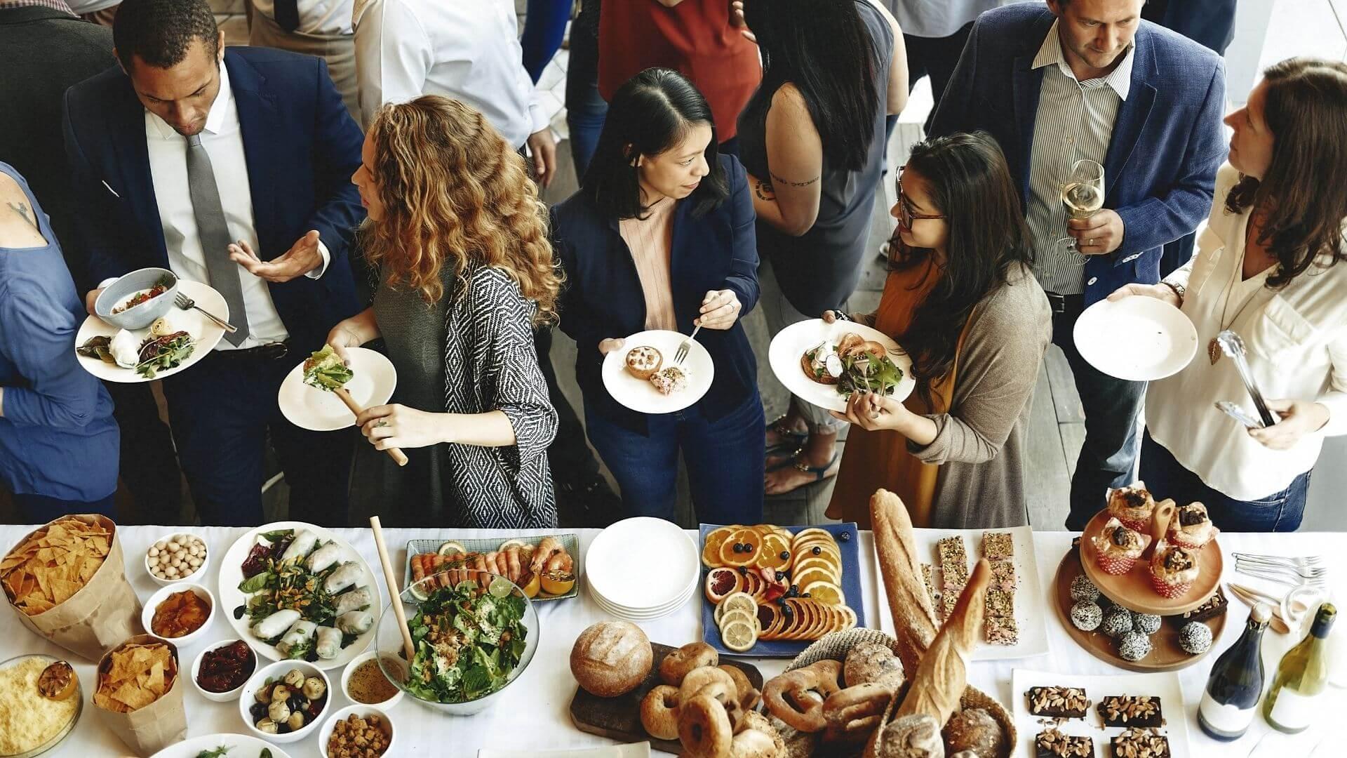 Essen und Trinken Stockfoto Buffet mit Menschen die davor stehen und essen und sich unterhalten shutterstock quadratisch copyright Rawpixel.com