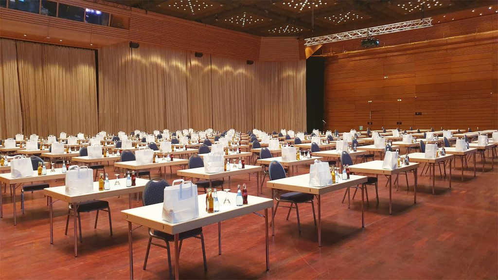Grosse Halle Saarlandhalle Coronabestuhlung eingedeckte Einzeltische mit Abstand dazwischen